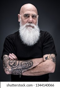 studio portrait of a senior hipster with tattooed arms, wearing a long white beard