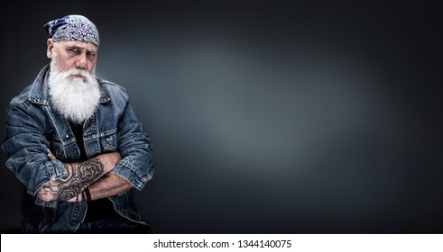 studio portrait of a senior hipster with tattooed arms, wearing a bandana and a long white beard. panoramic head