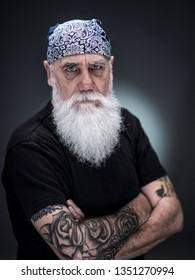 studio portrait of a senior hipster with tattooed arms, wearing a bandana and a long white beard