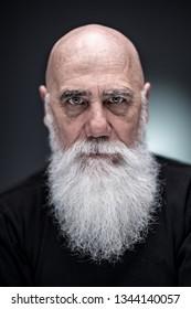 studio portrait of a senior hipster wearing a long white beard