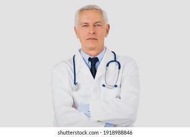 Studioporträt eines hohen männlichen Arztes, der auf isoliertem weißem Hintergrund steht.