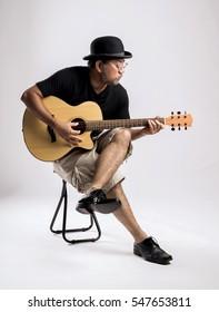 Studio portrait of senior man with hat playing guitar.