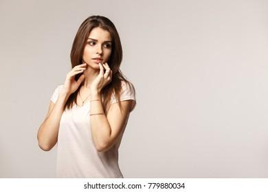 Studio portrait of sensual beautiful girl with dark hair in casual shirt.