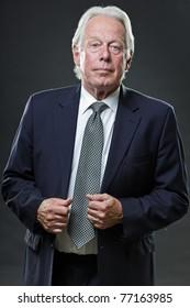 Studio portrait of serious senior business man in blue suit.