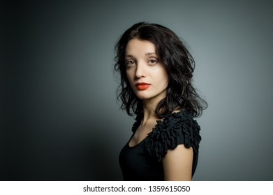 Studio portrait of sexy brunette woman with red sensual lips looking at the camera posing on black background