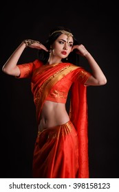 studio portrait of sexy girl in traditional Indian clothing and jeweleries. Beautiful Indian girl in traditional Indian sari. Young girl dressed in purple silk sari with jewels.