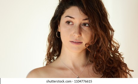 Studio portrait of sexy natural beauty with long curly hair wearing hoop earrings and neckchain looking away with slightly open lips over white background. She is attractive and sensual.
