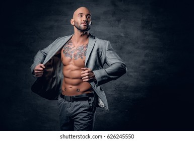 Studio portrait of shaved head tattooed male dressed in a grey jacket on a naked torso.