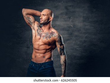 Studio portrait of shirtless shaved head, muscular male with tattoos on torso touch his head.