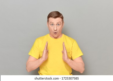 Studio portrait of shocked amazed blond mature man wearing yellow T-shirt, with widened eyes and open mouth, holding hands in front of him and showing size of something, standing over gray background