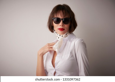 Studio portrait shot of fashionable woman wearing sunglasses and scarf while standing at light grey background.