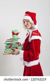 Studio portrait shot of slightly annoyed looking Santa Claus helper elf holding Christmas presents