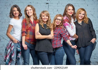Studio portrait of Six young happy attractive smiling caucasian women dressed in jeans grouped together