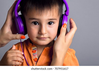 Studio portrait of a small funny boy with a woman's hands on headphones with music on a gray background, emotions of joy, surprise