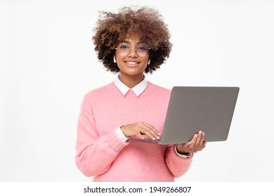 Studio portrait of smiling african american teen girl looking at camera, online course student holding laptop, isolated on gray background