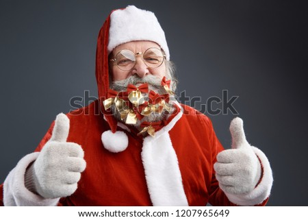 a84655960a5 Studio portrait of smiling old man in Santa costume showing thumbs up sign.  Isolated on