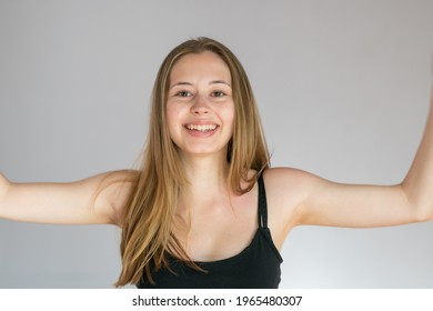 Studio portrait of a smiling young woman posing over a grey background showing her depilated armpits