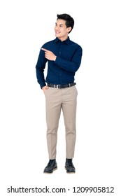 Studio portrait of sophisticated handsome smiling young Asian man wearing semi formal clothing while pointing at space aside