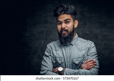 Studio portrait of stylish bearded Indian man in a blue shirt over grey background.