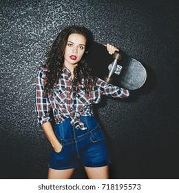 Studio portrait of stylish girl with skateboard