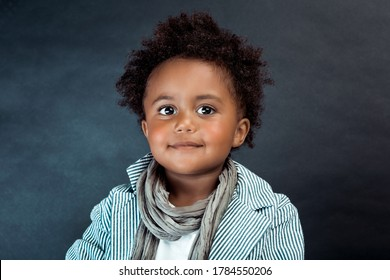 Studio Portrait of a Stylish Little African-American Boy with Curly Hair Isolated on Dark Background. Kids Fashion. Kids Clothes.