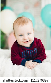 Studio portrait of sweet baby boy with big blue eyes, wearing in stylish clothes, lying on belly and looking at camera. Kid smiling, playing in white stylish decorated bedroom.