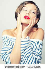 Studio portrait of a sweet girl with red lips in a vest