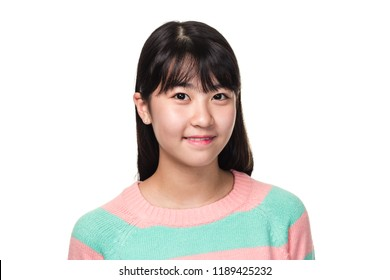 Studio portrait of a teenage East Asian woman smiling and looking somewhere