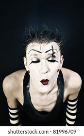 Studio portrait of a terrible clown with a dark makeup on  black background