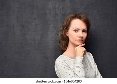 Studio portrait of thoughtful caucasian fair-haired girl, holding hand near chin, looking with serious expression at camera, standing half-turned against gray background, copy space on left