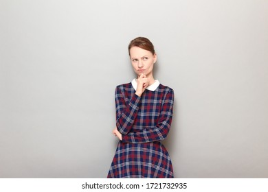 Studio portrait of thoughtful focused blond girl wearing checkered dress, looking aside, being deep in thoughts, trying to solve issue or make right choice, standing over gray background