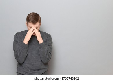 Studio-Porträt eines wohlüberlegten, müden, blonden Mannes, der einen Pullover trägt, eine berührende Nasenbrücke, versucht sich zu konzentrieren, leidet an Kopfschmerzen, steht über grauem Hintergrund, kopiert Platz auf rechts