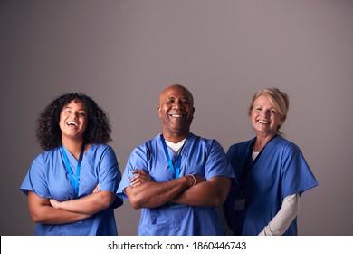Portrait De Studio De Trois Membres De L'Équipe Chirurgicale Portant Des Écrous Se Tenant Sur Fond Gris