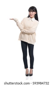 A studio portrait of a twenties Asian woman pointing at something and confidently introducing