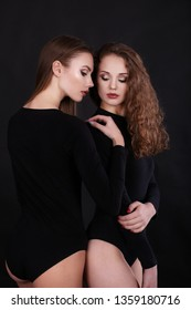 Studio portrait of two beautiful sexy   models in bodysuit. Beautiful two girls on a black background