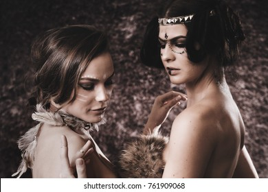 Studio portrait of two Caucasian female models in Native American clothing and makeup against a brown fur background