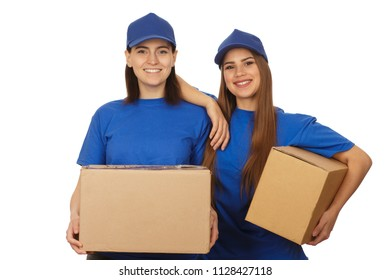 Studio portrait of two cheerful young female couriers wearing blue unifrom smiling to the camer joyfully holding cardboard boxes isolated. Teamwork, service, courier, profession concept