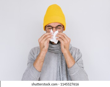 Studio portrait of unhealthy handsome man wearing grey sweater, yellow hat and glasses, blowing nose into tissue. Male have flu, virus or allergy. Healthy, medicine and people concept