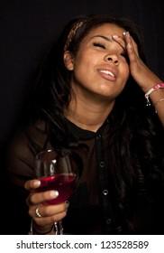 studio portrait of woman drinking wine ober black backdrop