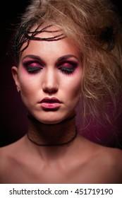 Studio portrait of woman in halloween makeup, black background.