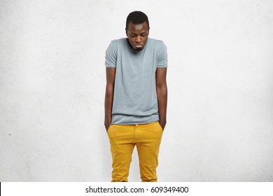 Studio portrait of young African male shrugging shoulders and looking down with guilty confused expression, keeping hands in pockets of his mustard pants. Human face expressions, emotions and feelings