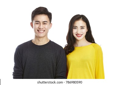 studio portrait of a young asian couple happy and smiling looking at camera, isolated on white background.