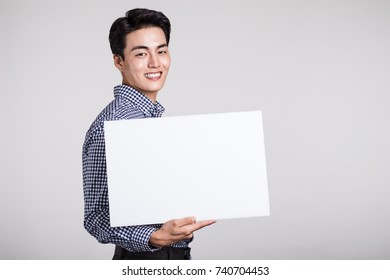 Studio portrait of a young asian man holding a billboard at gray background