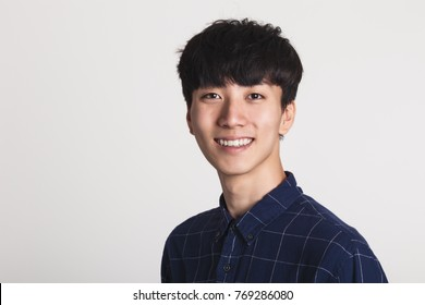 A studio portrait of a young Asian man making a confident smile