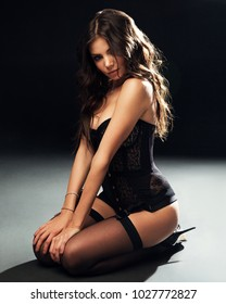 Studio portrait of young attractive brunette woman in black lingerie, corset, stockings sitting on black background, sexy female model posing, seduction and temptation concept, vertical, studio lights