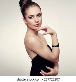 Studio portrait of young attractive fashion model with professional makeup and hair style wearing black dress with naked shoulders.