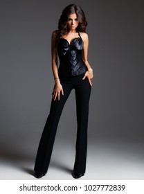 d8f7c9e66 Studio portrait of young attractive stylish brunette woman in black  trousers and corset standing on dark