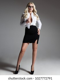 Studio portrait of young attractive woman with long curly blonde hair in white shirt, black skirt, high heels shoes, eyeglasses, top with decollete standing on grey background, sexy secretary concept