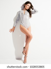 Studio portrait of young attractive woman model with brunette long curly hair, in silver bodysuit dress and high heels, long legs with tan skin, slim body, standing on background with sun hard light