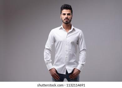 Studio portrait of young bearded serious man wearing white shirt